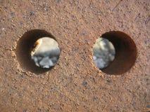 Deux trous dans l'abrégé sur brique image stock