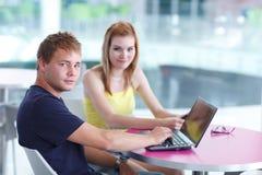 Deux étudiants universitaires ayant l'amusement étudier ensemble Photographie stock libre de droits