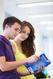 Deux étudiants universitaires dans la bibliothèque Photos stock