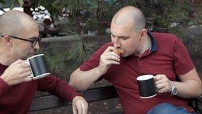 Deux types chauves s'asseyent en parc et mangent des sandwichs et des pommes frites, café potable, parlant Nourriture délicieuse clips vidéos