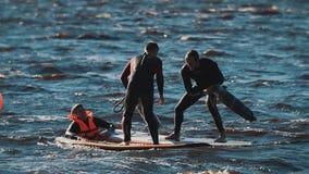 Deux types combattant avec les tapis roulés se tenant sur le conseil surfant dans l'eau onduleuse clips vidéos