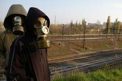 Deux types dans les masques, restant contre un contexte de Images stock