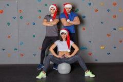 Deux types et une fille dans des chapeaux de Santa posant contre le mur pour s'élever image libre de droits