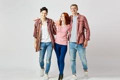 Deux types et une fille dans des vêtements colorés lumineux élégants marchent et sourient sur le fond blanc dans le studio images stock