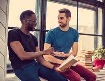 Deux types lisant un livre dans une chambre Image libre de droits