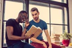 Deux types lisant un livre dans une chambre Photographie stock libre de droits
