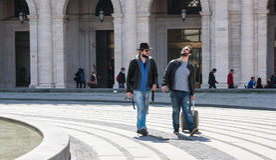 Deux types marchent par les rues de Gênes, Italie et regardent autour, parlant entre eux Image libre de droits