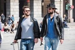 Deux types marchent par les rues de Gênes, Italie et regardent autour, parlant entre eux Photo stock