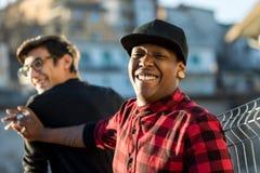 Deux types plaisantant et riant sur la rue Photo stock