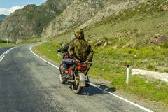 Deux types sans casques montent sur une vieille moto rouge soviétique dessus image libre de droits