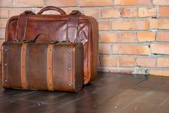 Deux valises en cuir brunes sur le plancher en bois contre le mur de briques Rétro conception de bagages Concept de course et de  images libres de droits