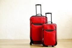 Deux valises rouges colorées de la même taille différente aimable avec la poignée télescopique sur le plancher en bois, fond blan photographie stock libre de droits