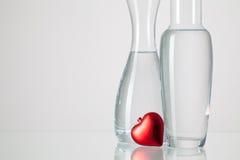 Deux vases avec de l'eau propre et le coeur rouge Photos stock
