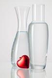 Deux vases avec de l'eau propre et le coeur rouge Photo libre de droits