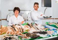 Deux vendeurs posant près de l'affichage avec les poissons congelés Photos stock