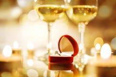 Deux verres à vin de vin et la boîte rouge avec la bague de fiançailles au-dessus du fond de bokeh Image stock