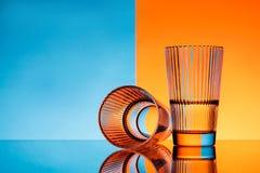 Deux verres avec de l'eau au-dessus de fond bleu et orange Images libres de droits