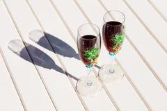 Deux verres avec du vin sur une table blanche près de la piscine Images stock