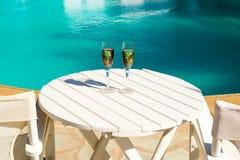 Deux verres avec du vin sur une table blanche près de la piscine Images libres de droits