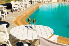 Deux verres avec du vin sur une table blanche près de la piscine Photographie stock