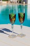Deux verres avec du vin sur une table blanche près de la piscine Photographie stock libre de droits