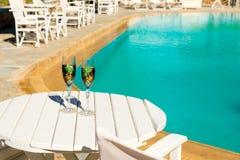 Deux verres avec du vin sur une table blanche près de la piscine Image stock