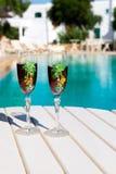 Deux verres avec du vin sur une table blanche près de la piscine Photo stock