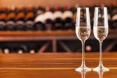 Deux verres avec le champagne à l'arrière-plan avec des bouteilles de vin Photographie stock libre de droits
