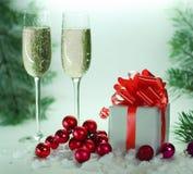 Deux verres avec le champagne, et les boîtes avec des cadeaux sur le Ba de Noël Photos stock