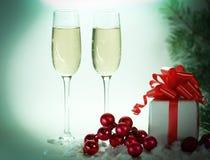 Deux verres avec le champagne, et les boîtes avec des cadeaux sur Noël b Photo stock