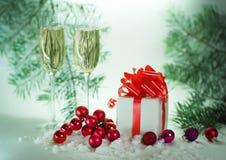 Deux verres avec le champagne, et les boîtes avec des cadeaux sur Noël b Images stock