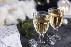 Deux verres avec le champagne et les mandarines et présents au fond noir images stock