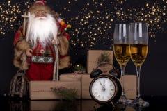 Deux verres avec le champagne, la Santa Claus et les cadeaux de Noël images libres de droits