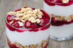Deux verres avec le dessert posé avec du yaourt, la granola et la cerise Photo stock