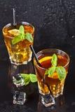 Deux verres avec le thé glacé traditionnel froid avec le citron, les feuilles en bon état et les glaçons photographie stock
