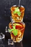 Deux verres avec le th? glac? traditionnel froid avec le citron, les feuilles en bon ?tat et les gla?ons photos stock
