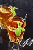 Deux verres avec le th? glac? traditionnel froid avec le citron, les feuilles en bon ?tat et les gla?ons photo stock