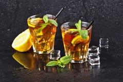 Deux verres avec le th? glac? traditionnel froid avec le citron, les feuilles en bon ?tat et les gla?ons image libre de droits