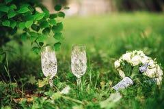 Deux verres cristal et un bouquet des fleurs se trouvant sur l'herbe Image stock