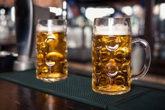 Deux verres de bière sur une table de barre Robinet de bière sur le fond Photo stock