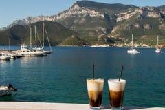 Deux verres de café froid par la vue de paysage marin Image stock
