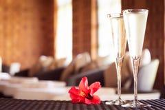 Deux verres de champagne avec la fleur rouge dans un salon de station thermale Ti de station thermale Photographie stock libre de droits