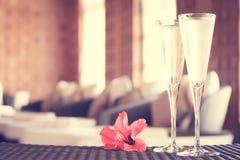 Deux verres de champagne avec la fleur rouge dans un salon de station thermale Ti de station thermale Photos stock