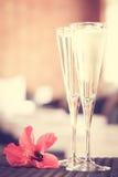 Deux verres de champagne avec la fleur rouge dans un salon de station thermale Ti de station thermale Images stock