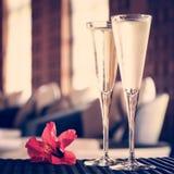 Deux verres de champagne avec la fleur rouge dans un salon de station thermale Ti de station thermale Photographie stock