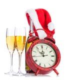 Deux verres de champagne, chapeaux de Santa, bouteilles et horloges Photographie stock libre de droits