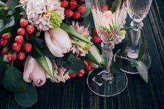 Deux verres de champagne et bouquet des fleurs roses sur l'obscurité courtisent images stock