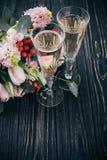 Deux verres de champagne et bouquet des fleurs roses sur l'obscurité courtisent image stock