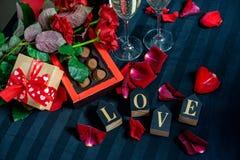 Deux verres de champagne, de roses rouges, de pétales, de boîte-cadeau avec le ruban rouge, de chocolats et de mots en bois d'amo image stock