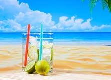 Deux verres de cocktail avec la tranche de chaux sur la plage et la paume de tache floue Photos stock